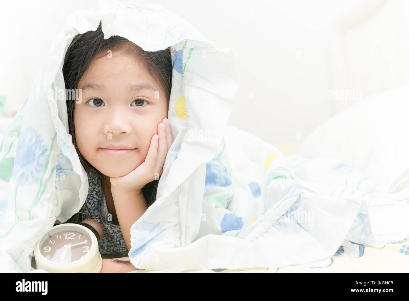 Adorable little cute girl awaked up in her bed with alarm clock - Stock Image