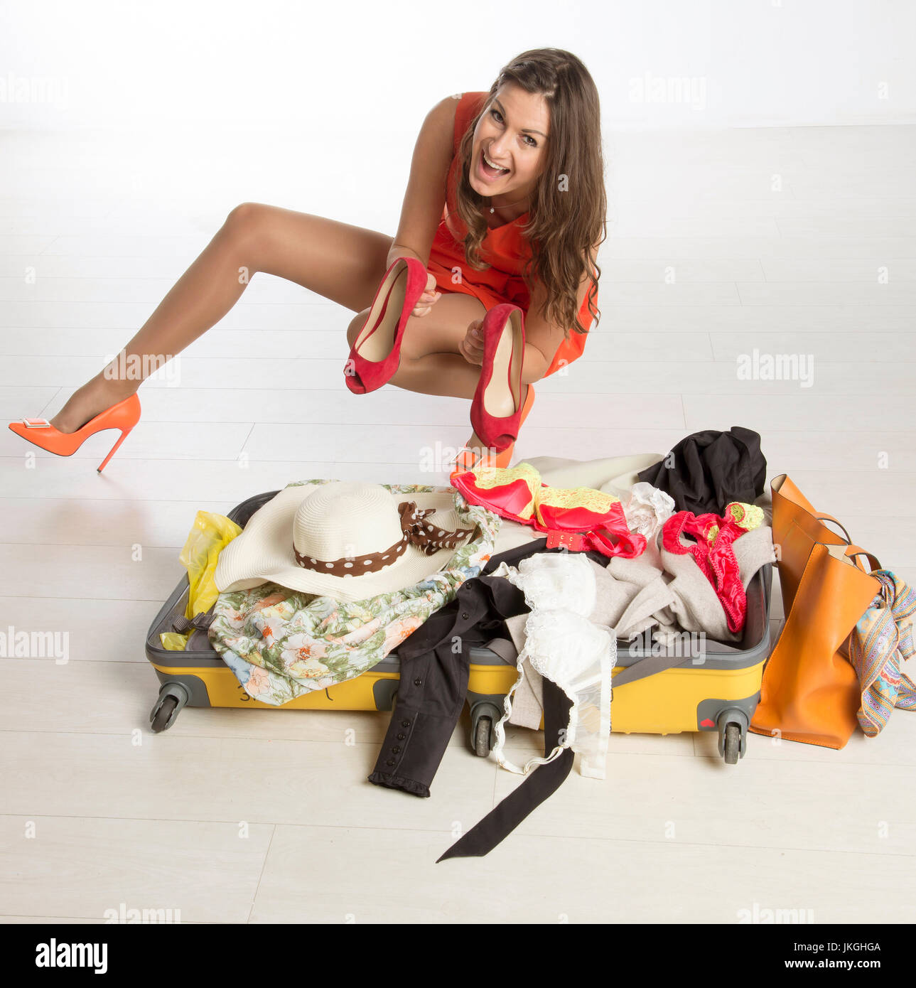 Holidaymaker packing a suitcase, summer clothing and a large hat - Stock Image
