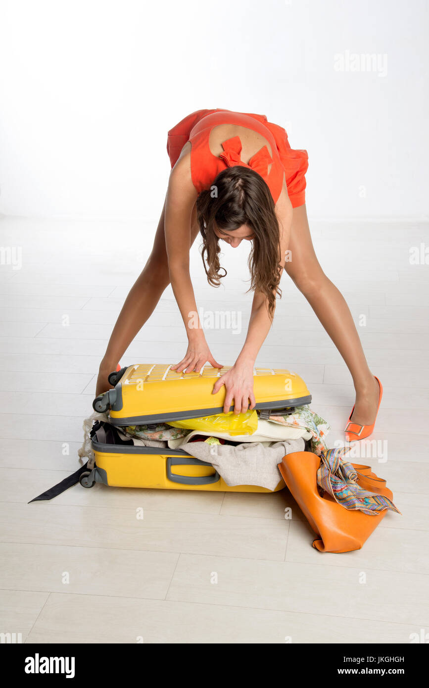 Holidaymaker trying to close her suitcase - Stock Image