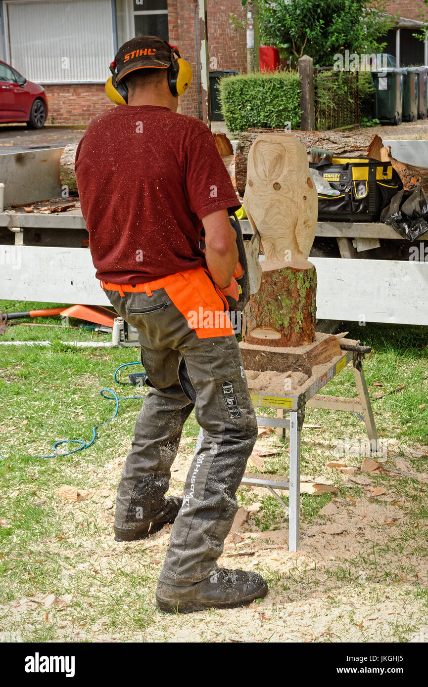 Artist carving an owl from a log of wood using a chain saw - Stock Image