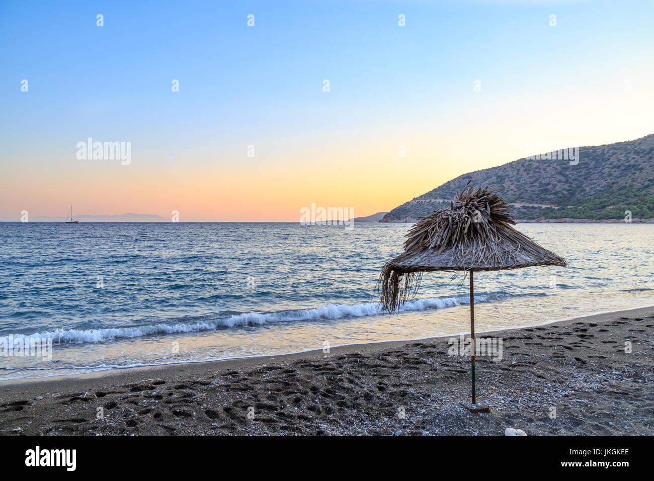 Straw umbrella on the beach during sunset - Stock Image