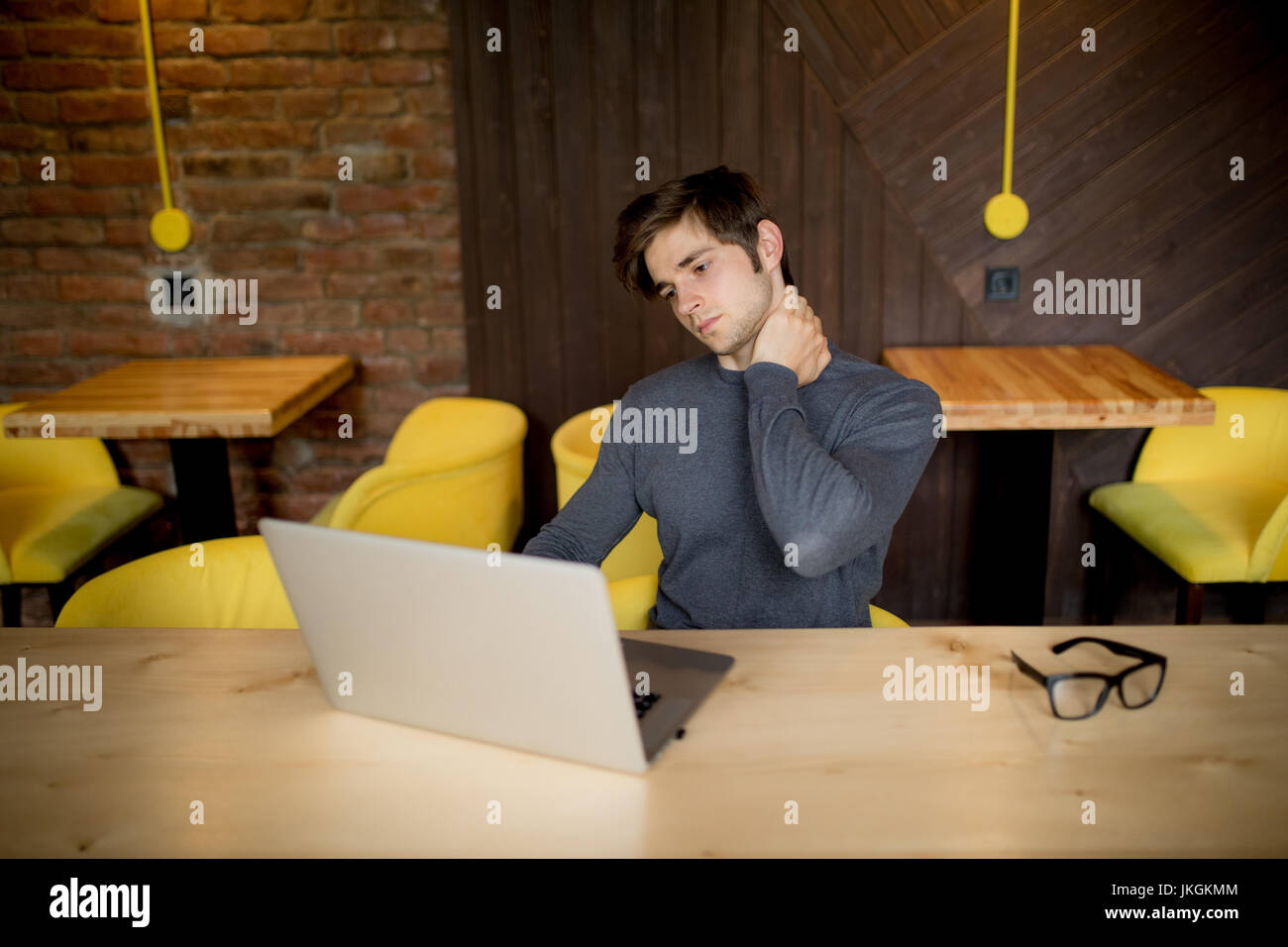 Handsome man suffering from neck pain in office - Stock Image
