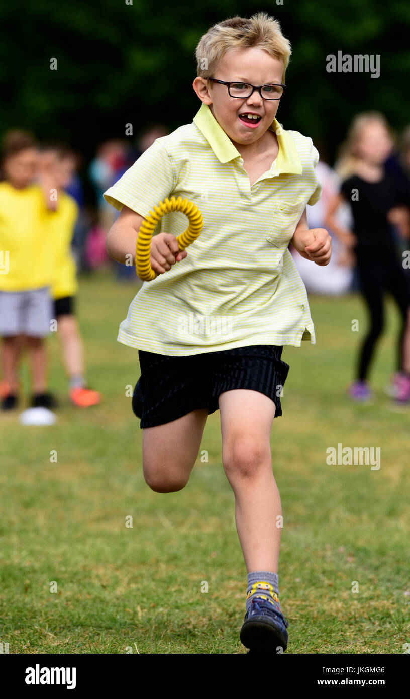 Six year old boy competing in relay running event at an infant school sports day, Bordon, Hampshire, UK. 14 July - Stock Image