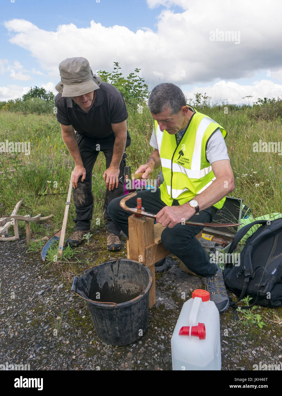 Instructor watching Sustrans volunteer sharpen a scythe by peening the blade, England, UK - Stock Image