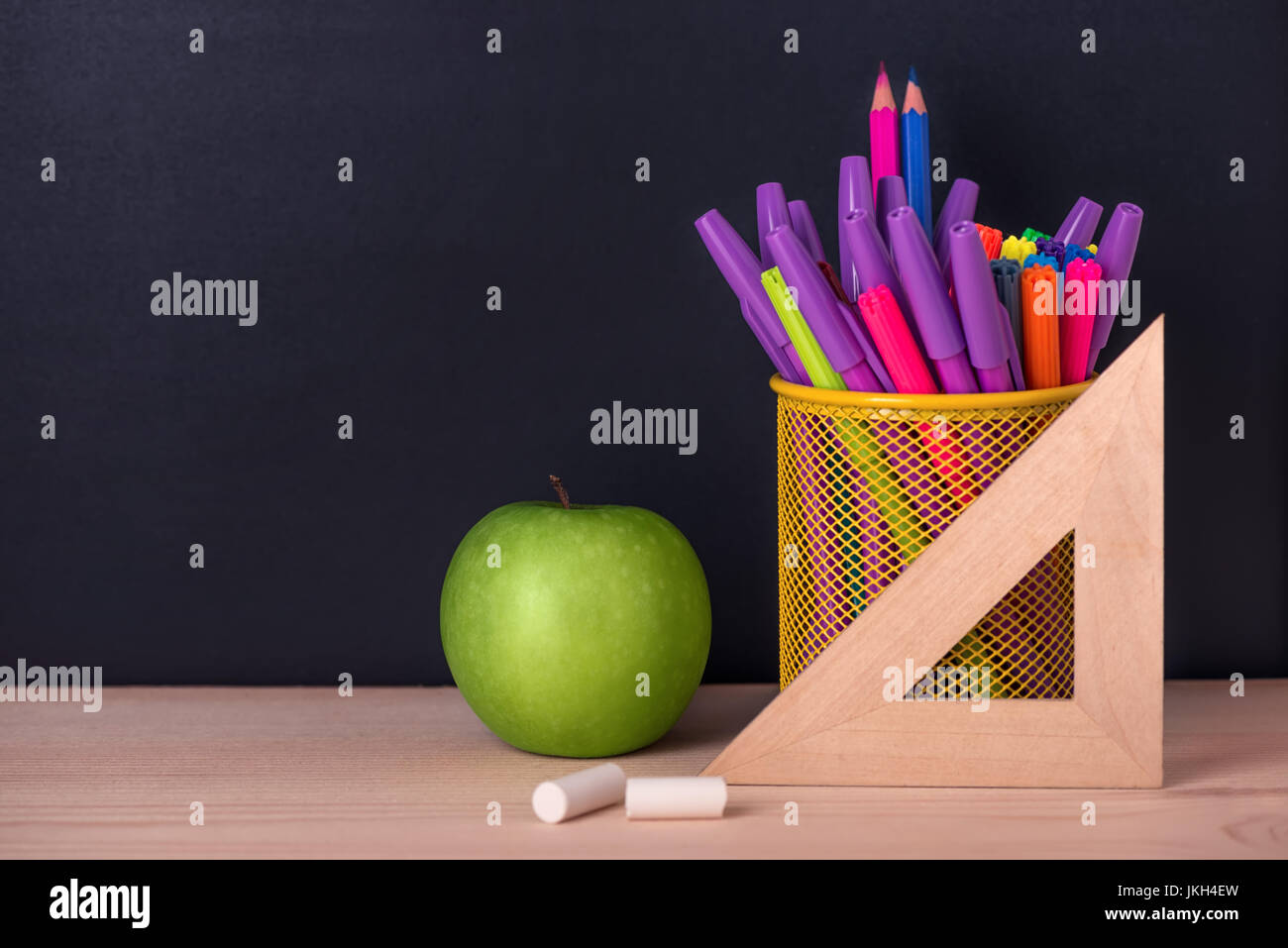 Education Concept With Green Apple Ruler Or Triangle Felt Pens Chalks Over Black Chalkboard Background Close Up