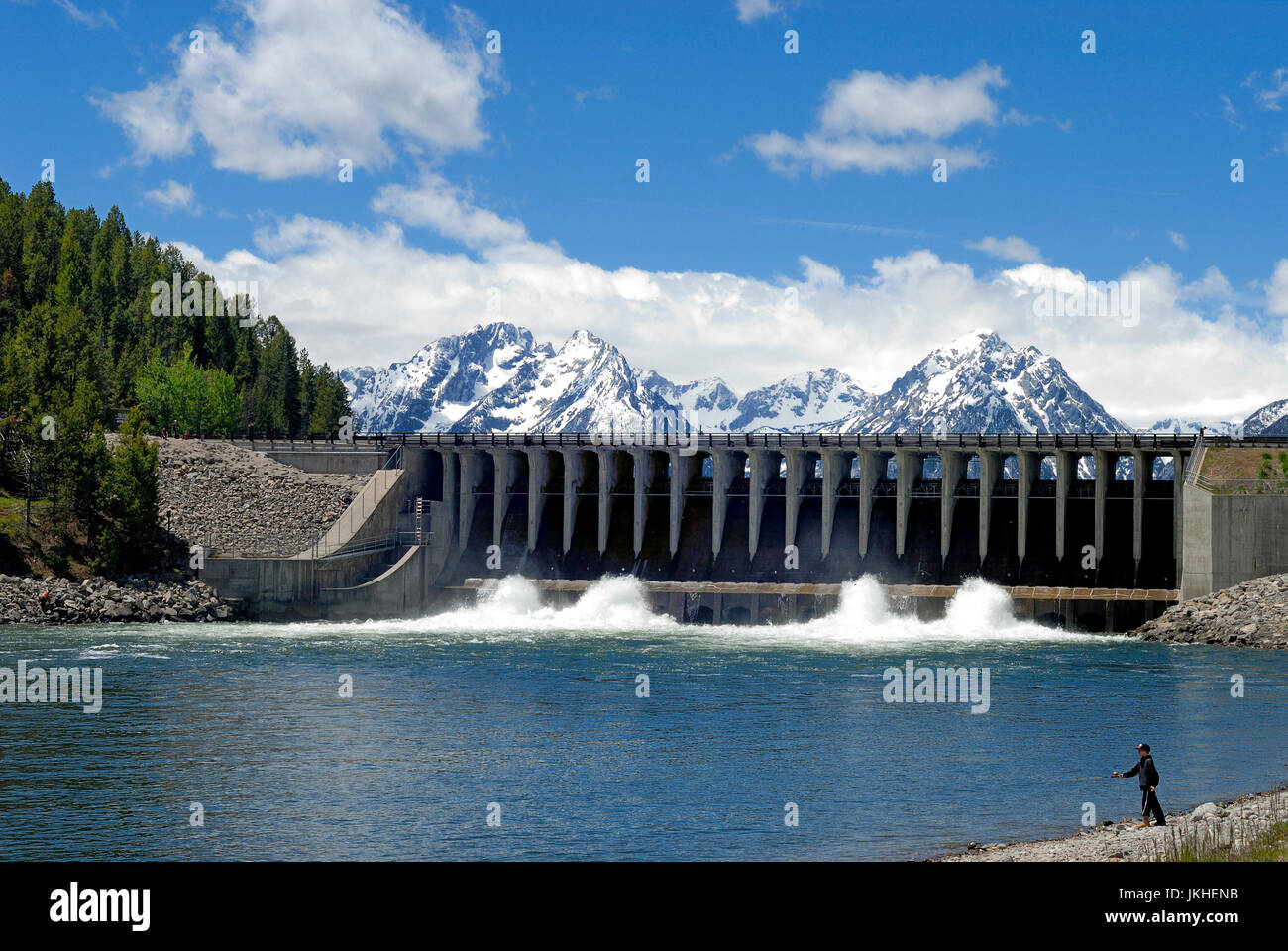 A boy fishes while water releases from Jackson Lake Dam on Jackson Lake, Grand Teton National Park - Stock Image