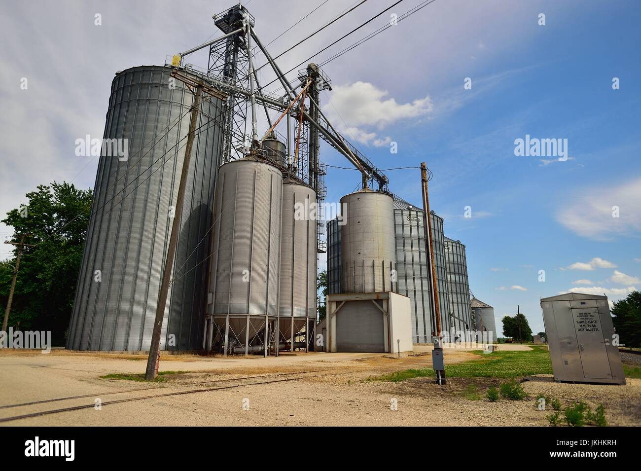 Lee, Illinois, USA. A series of storage tanks form a cooperative sitting along side a railroad siding in a small - Stock Image