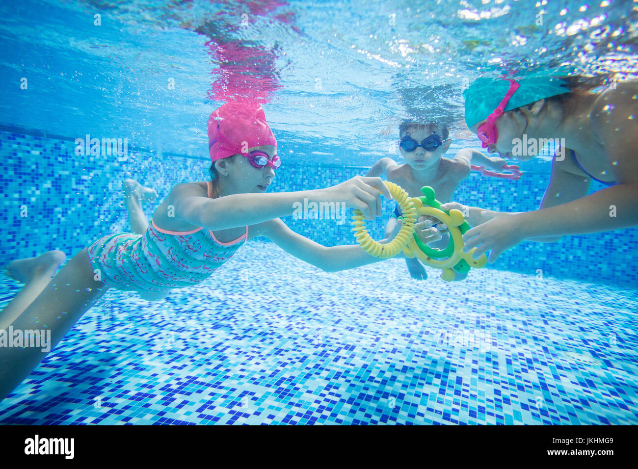 Kids swimming underwater and playing with toys in swimming pool Stock Photo