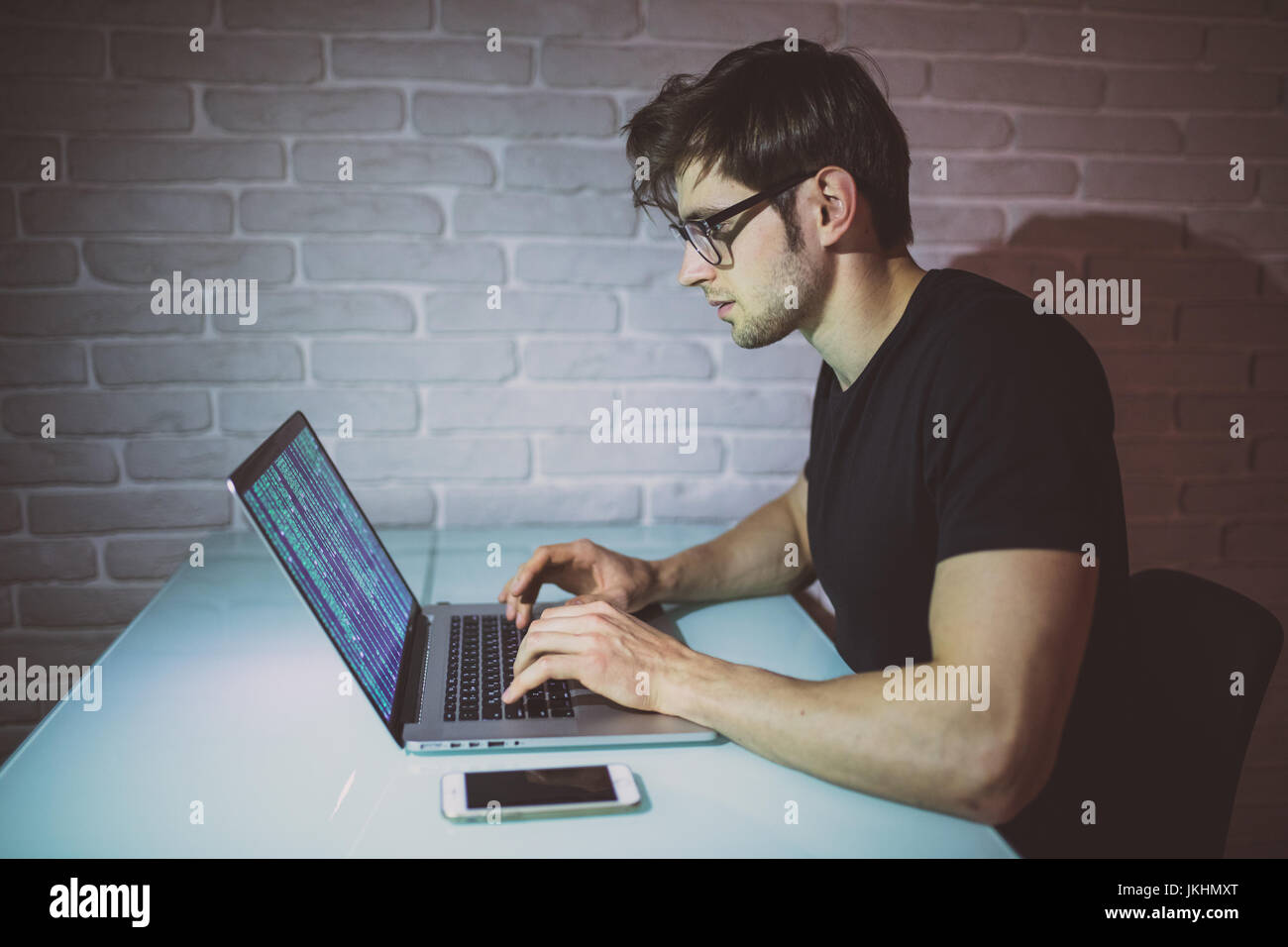 Young man programer work on laptop in the night and hack the network. Young hacker attack a network in the night. - Stock Image