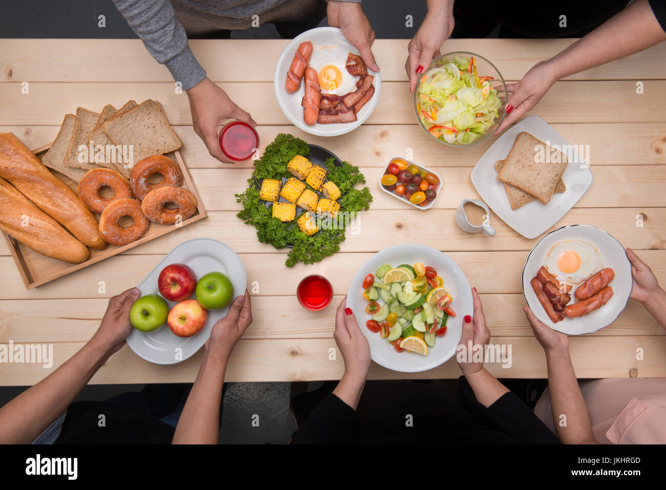 Enjoying dinner with friends.  Top view of group of people having dinner together while sitting at wooden table - Stock Image