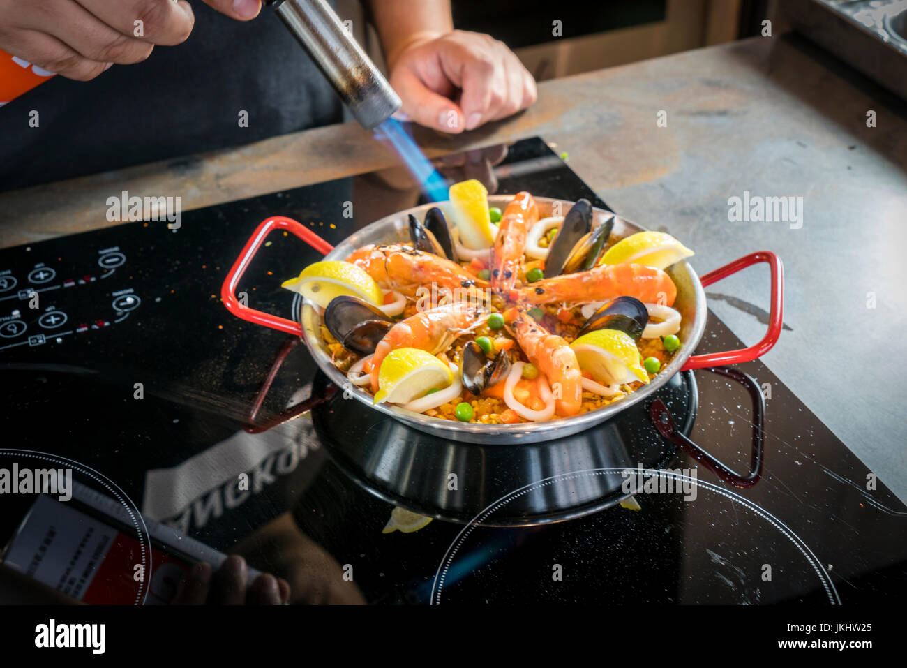 Chef is frying seafood of paella with burner - Stock Image
