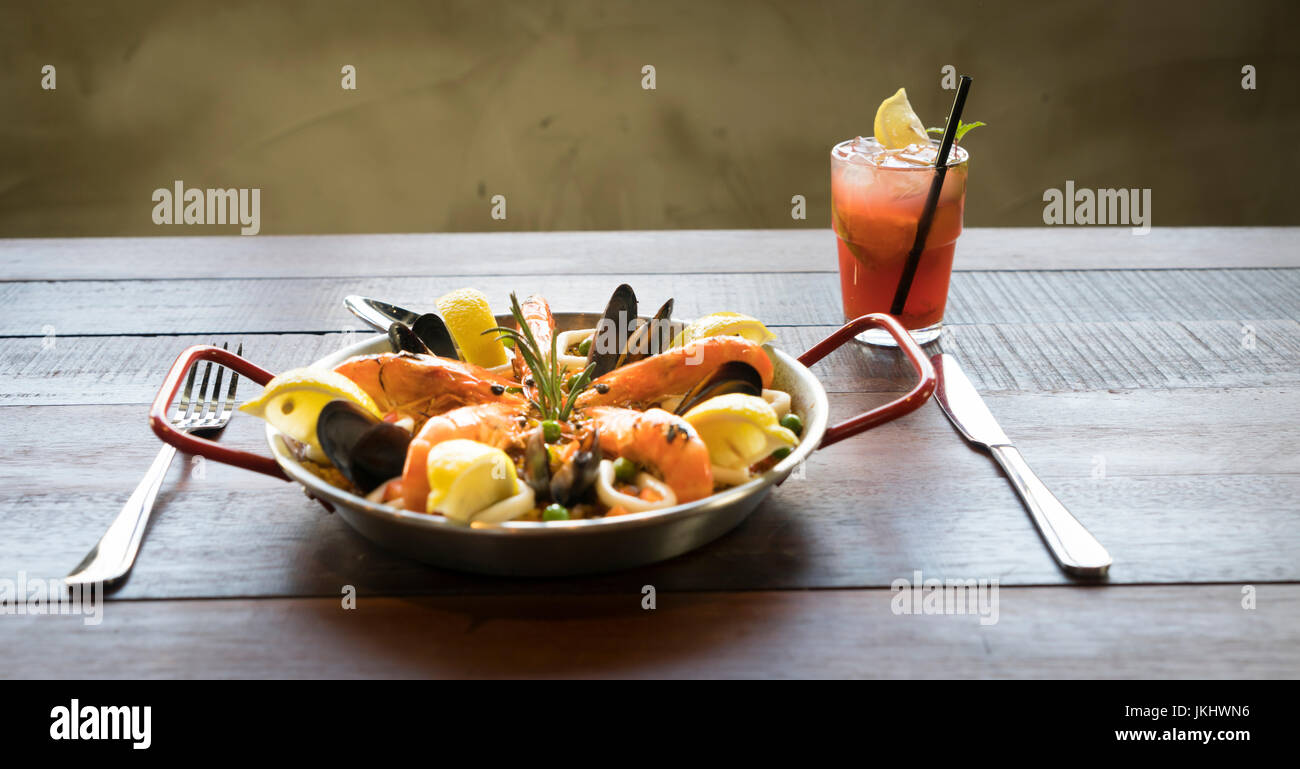 Paella with seafood vegetables and saffron served in the traditional pan - Stock Image
