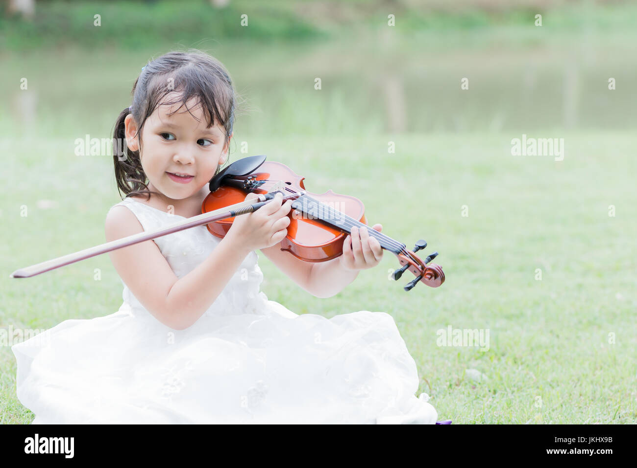 cute asian girl play violin in park or nature background. Stock Photo