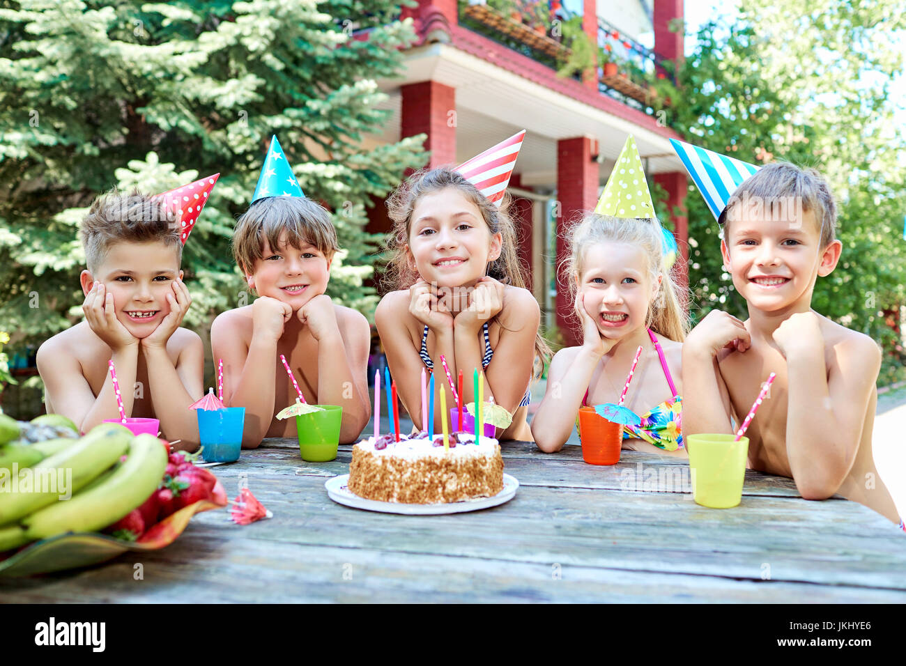 A group of children in swimsuits celebrates a birthday in the su - Stock Image