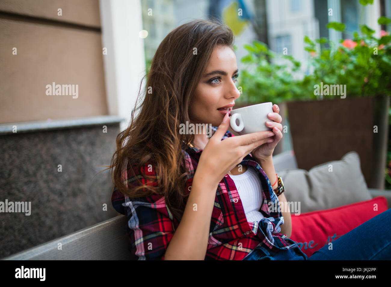 woman in city cafe drink coffee wait for somebody in cafe - Stock Image
