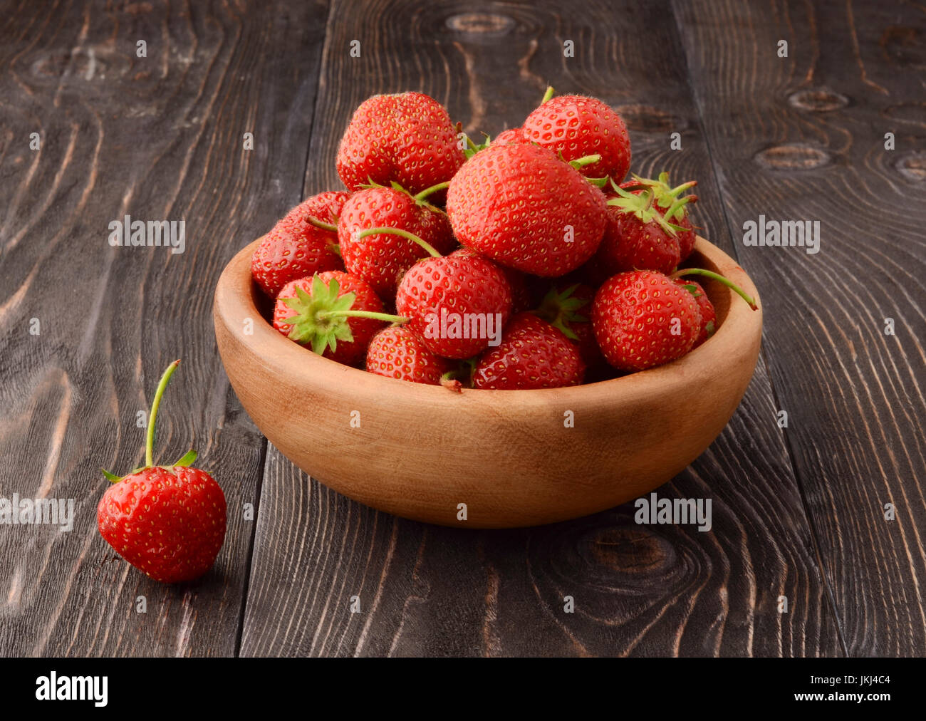 Ripe strawberries in wooden bowl and green leaves on old table, top view - Stock Image