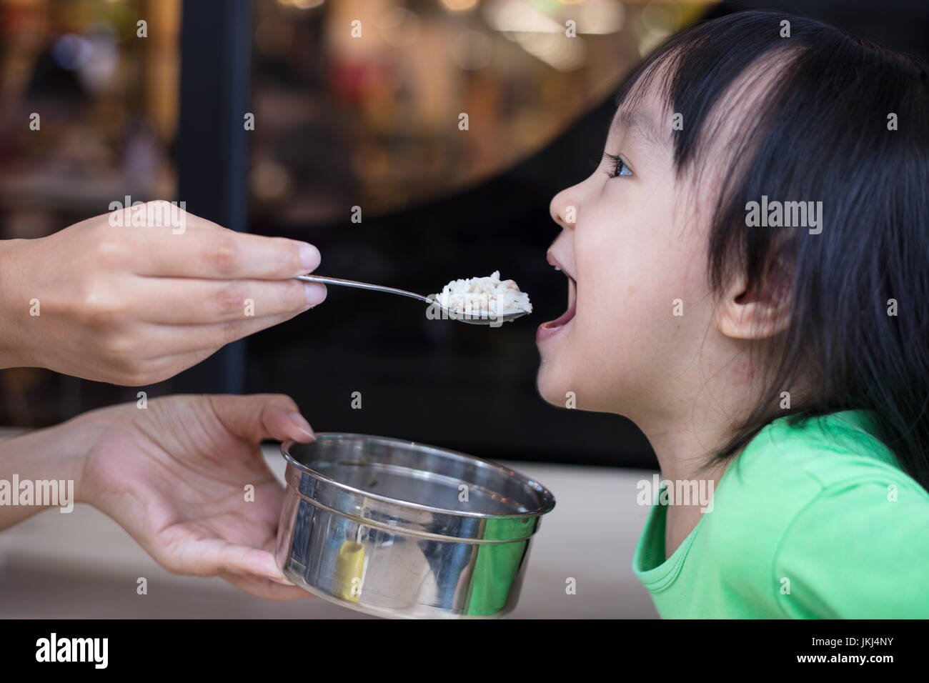 Asian Chinese little girl eating steamed minced pork and rice at outdoor restaurant - Stock Image