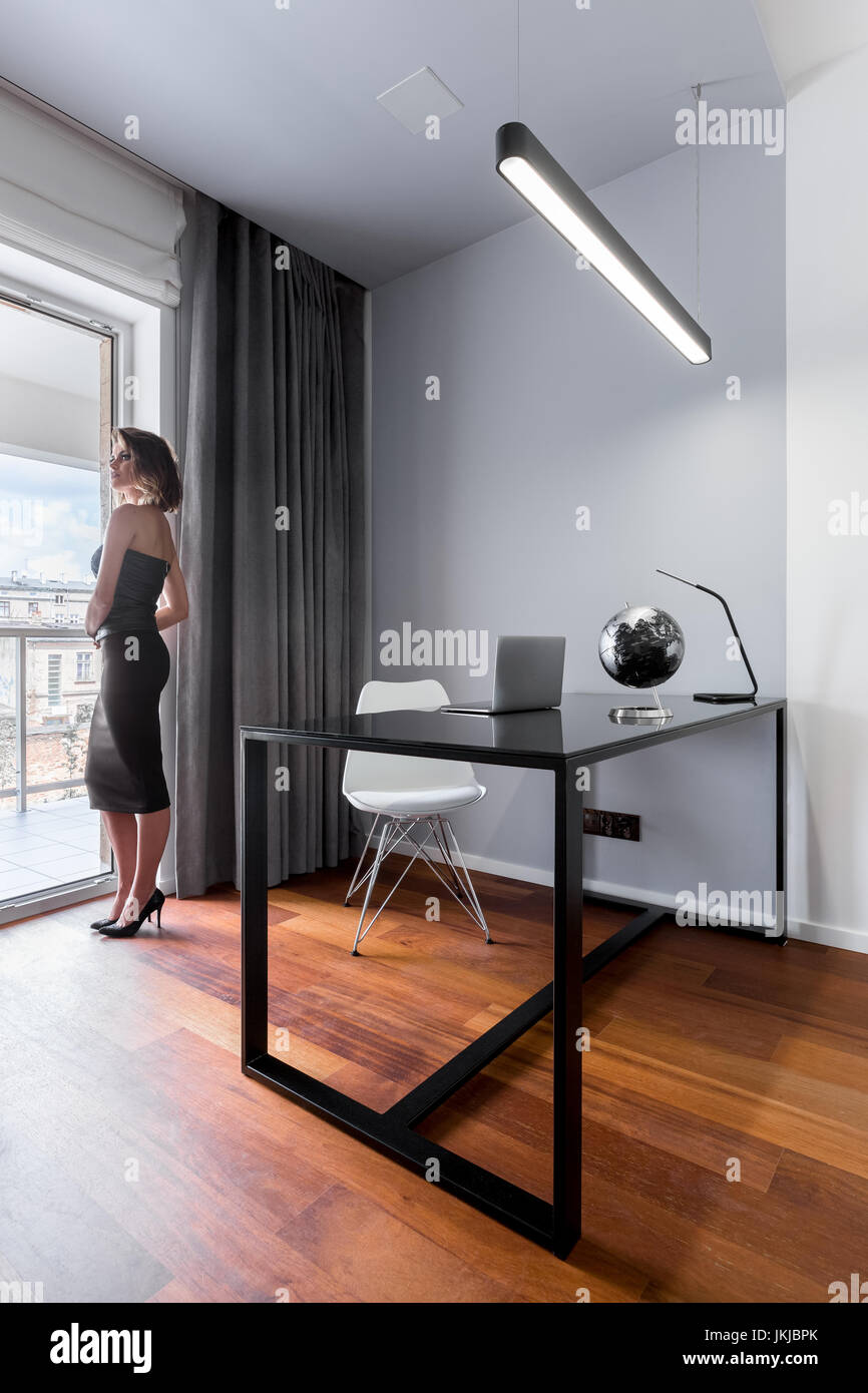 simple minimalist home office. Woman Standing In Minimalistic Home Office With Black Table And White Chair Simple Minimalist G