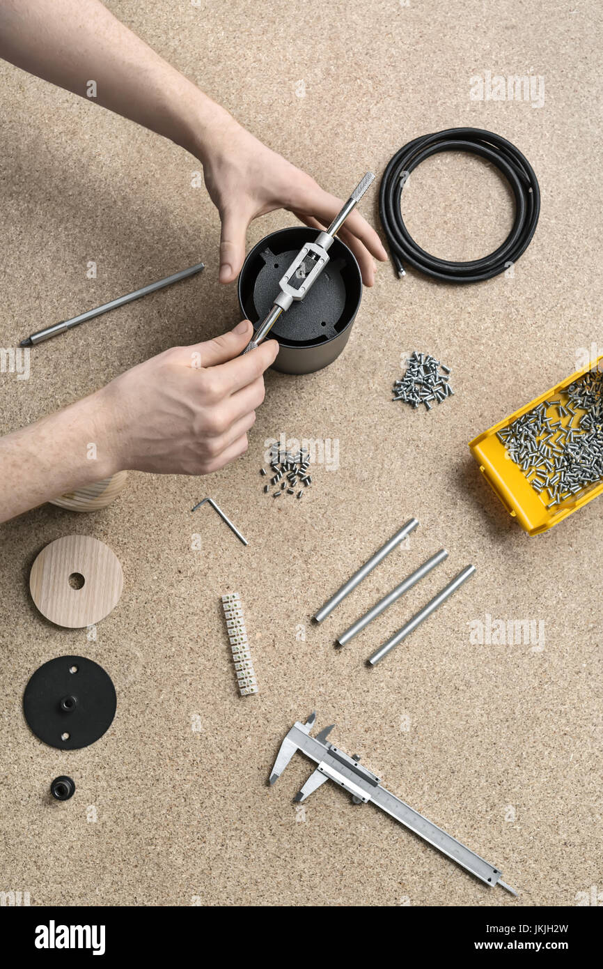 Guy using wrench in workshop - Stock Image