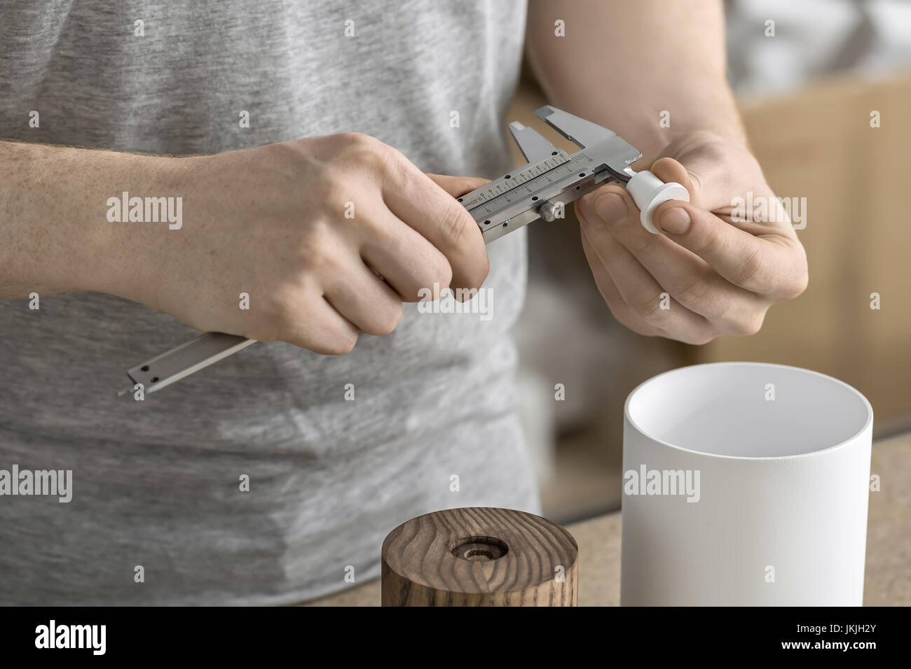 Man using caliper in workshop - Stock Image