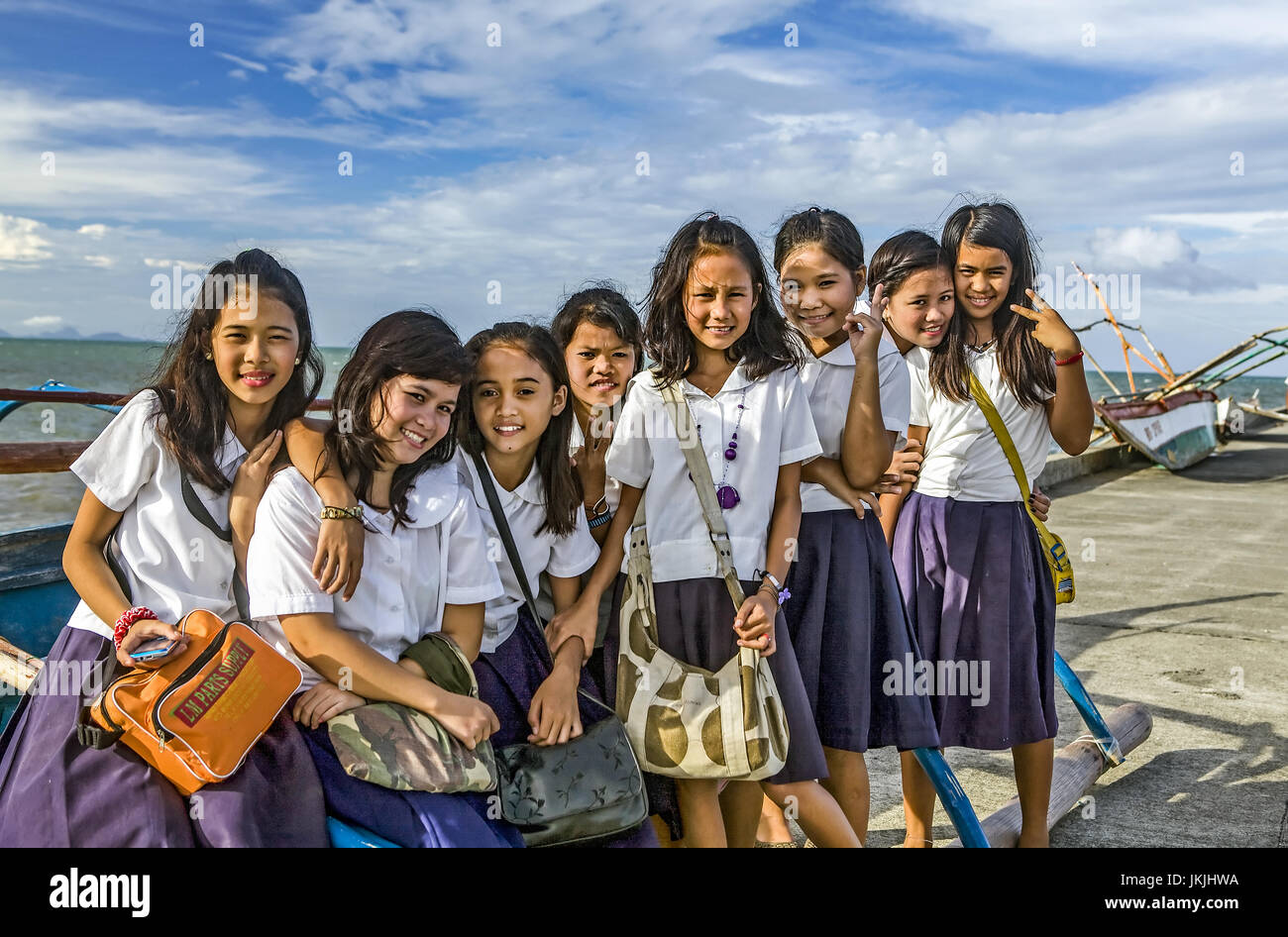Happy girl children in uniforms from the Philippines on their way to school. - Stock Image
