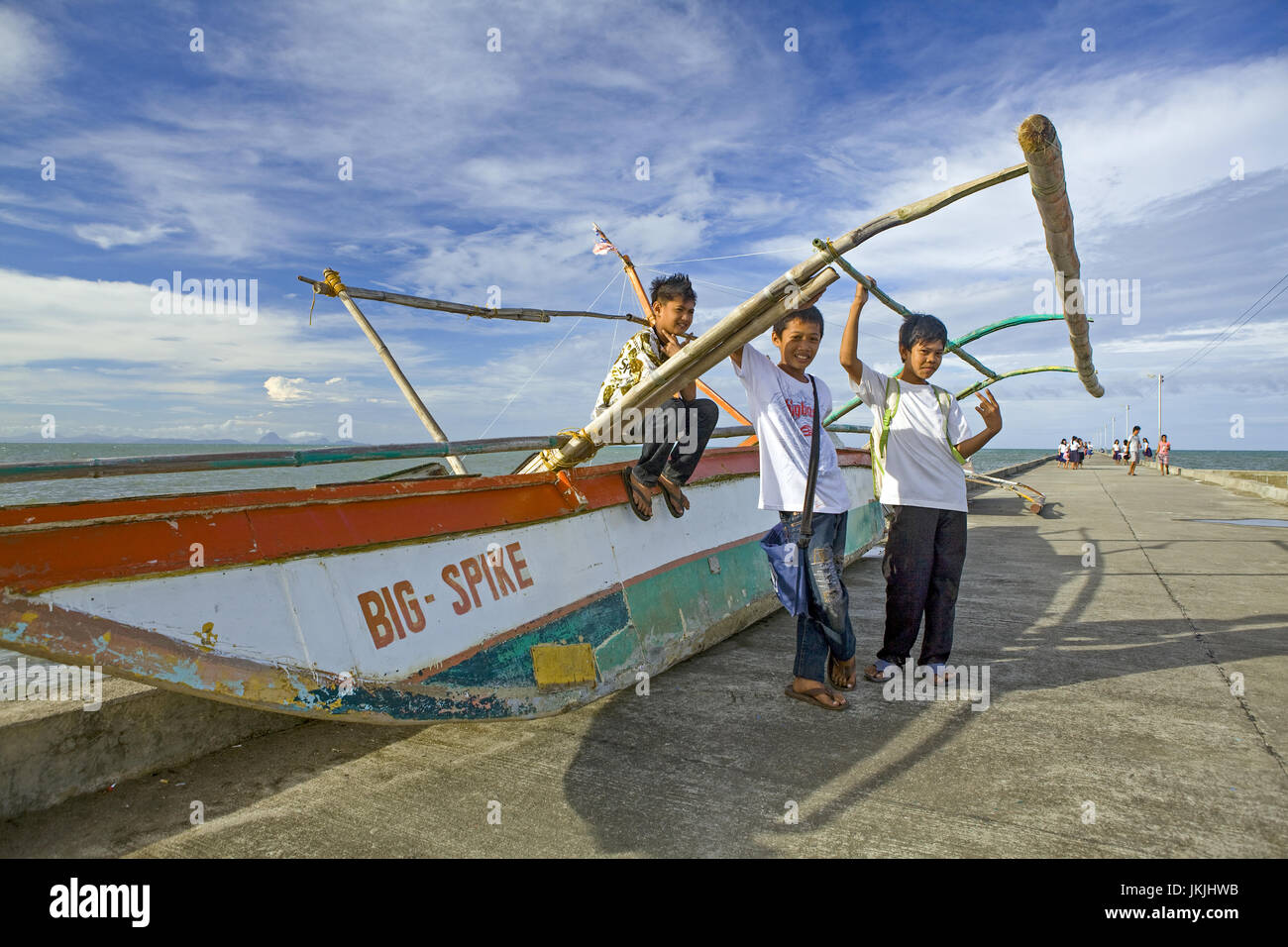 Three Filipino schoolboys hang out on the pontoon of an outrigger canoe after school in Cadiz City, Negros Oriental - Stock Image