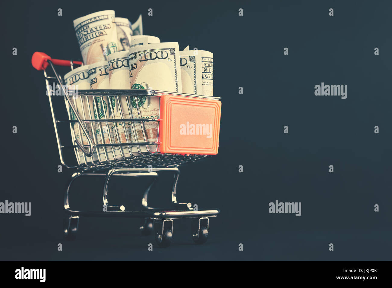 Shopping cart filled with one hundred dollar bill rolls, shallow depth of field, color toning applied. - Stock Image