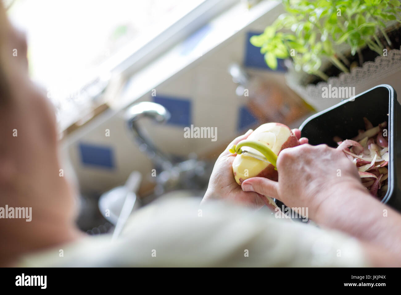 Senior woman peeling red potatoes, preparing food. Horizontal orientation with selective focus on potatoe and peeler. - Stock Image