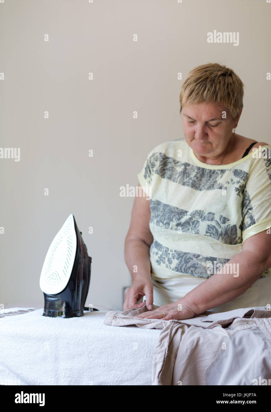 Senior woman ironing washed cloths in light room. Vertical orientantion with selective focus on working hands with - Stock Image