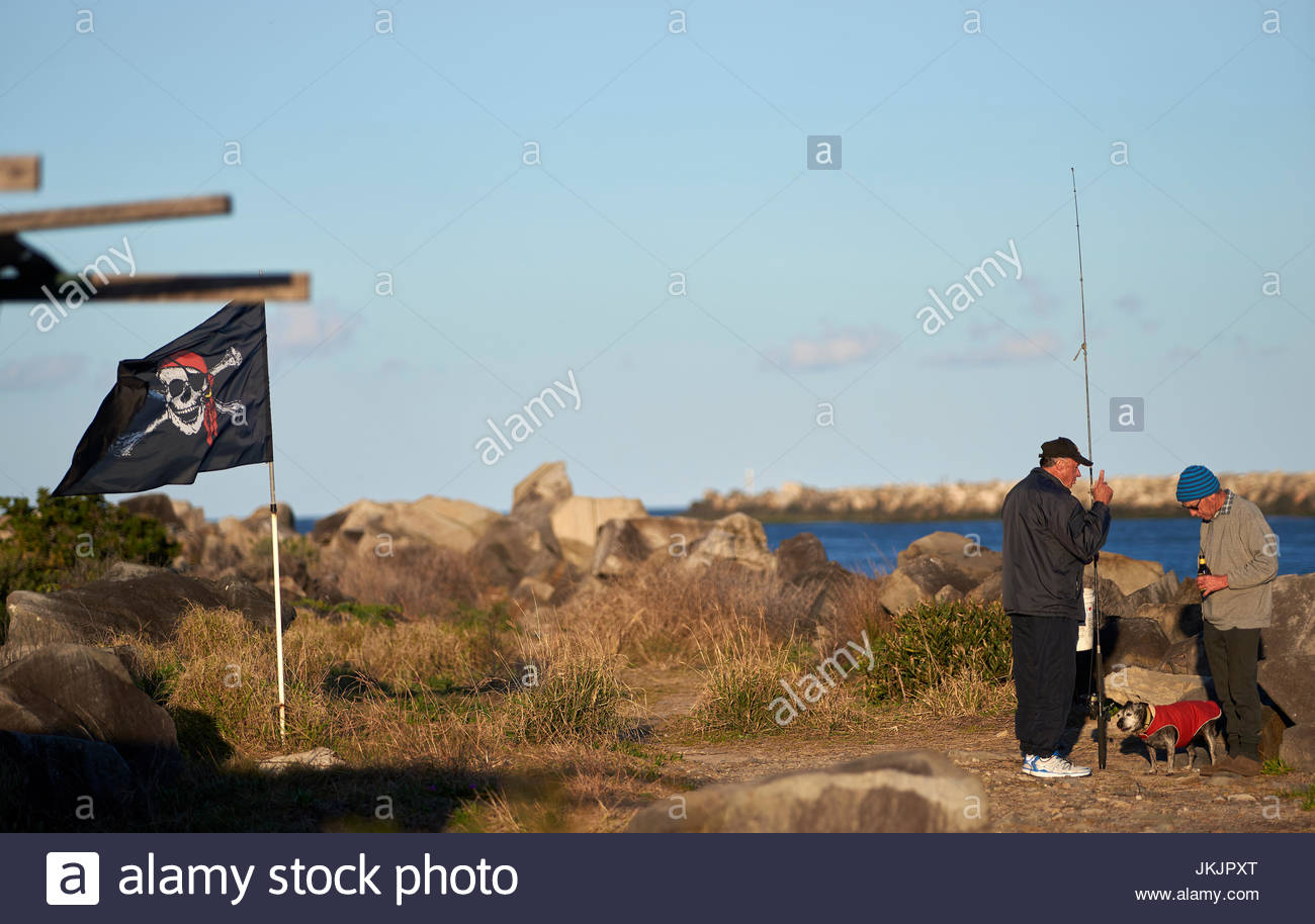 Two fishermen having a chat, beside the Clarence River; with a dog and a Jolly Roger flag. - Stock Image
