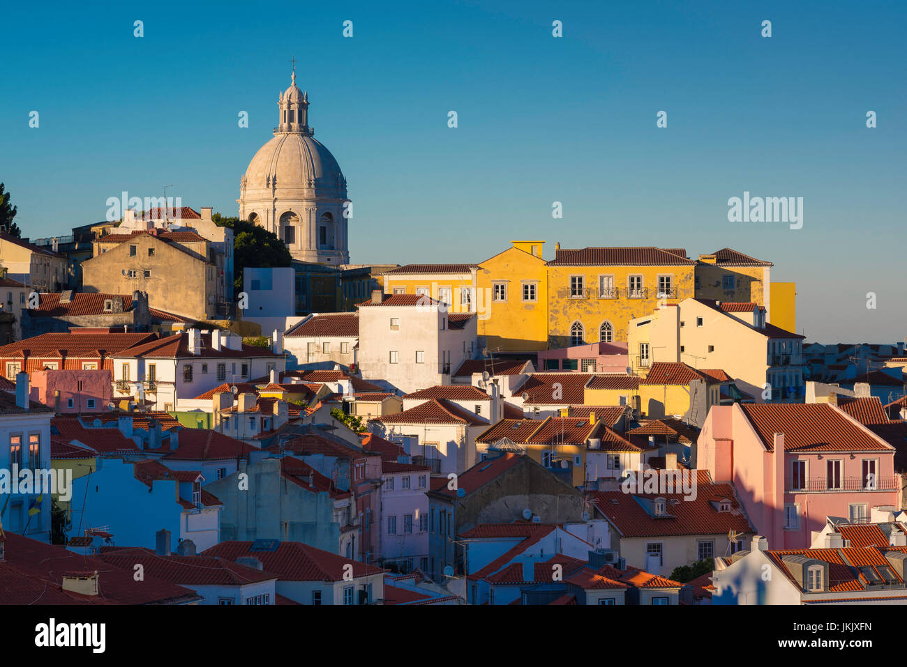 Lisbon cityscape, view of the Alfama skyline at sunset with the dome of the National Pantheon rising above the rooftops, - Stock Image