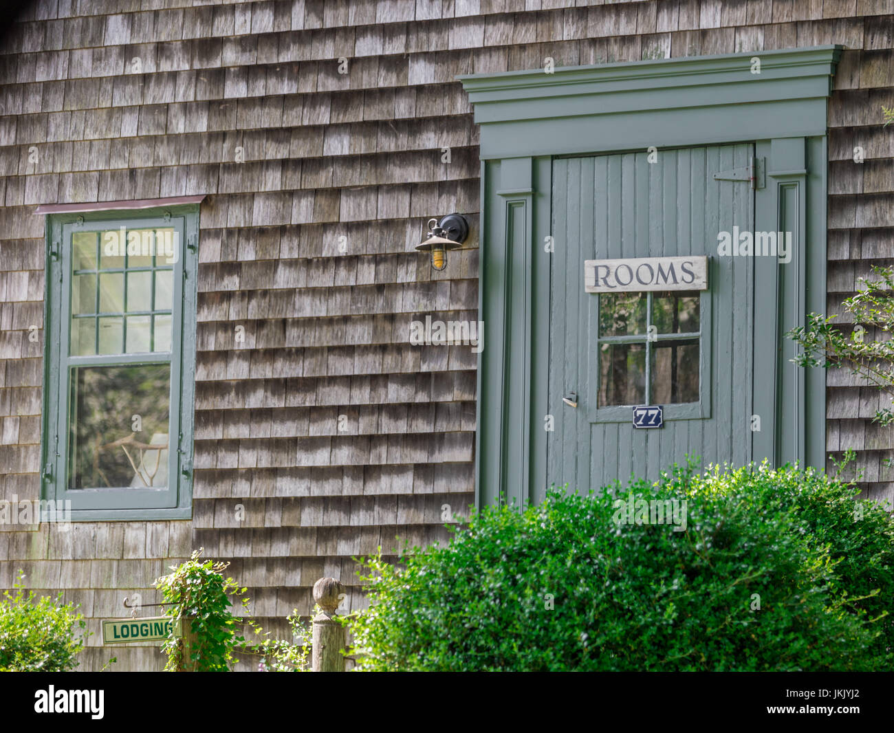 old home with a sign on the front door advertising rooms, lodging in East Hampton, NY - Stock Image