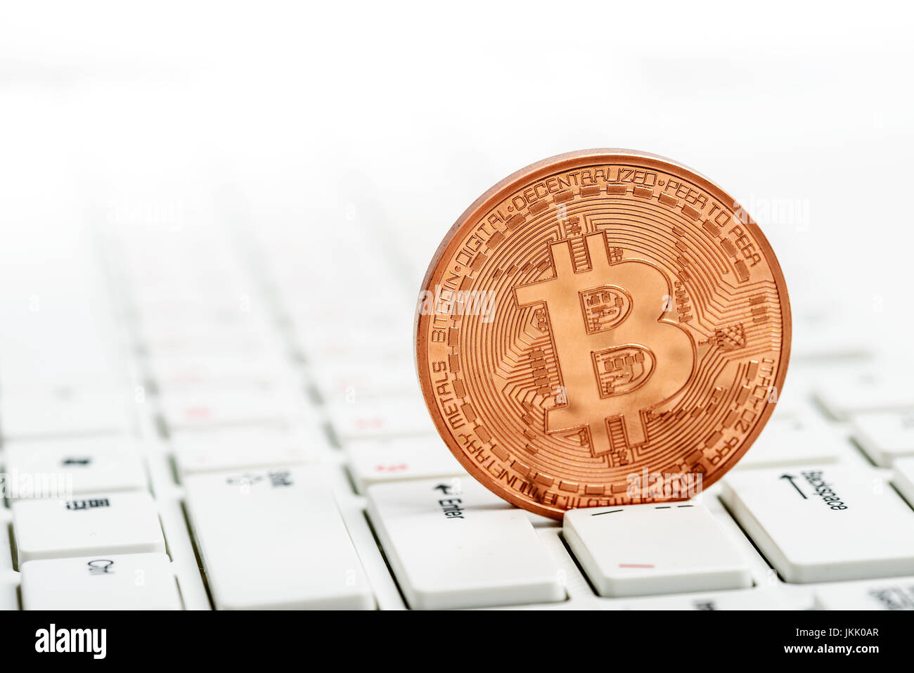 Bitcoin coin on white keyboard and money - Stock Image