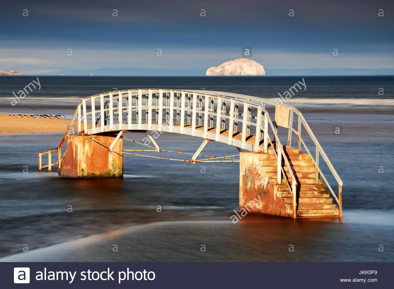 The bridge to nowhere from the shore of Belhaven bay with the Bass rock in the distance, Dunbar, North Berwick. Stock Photo