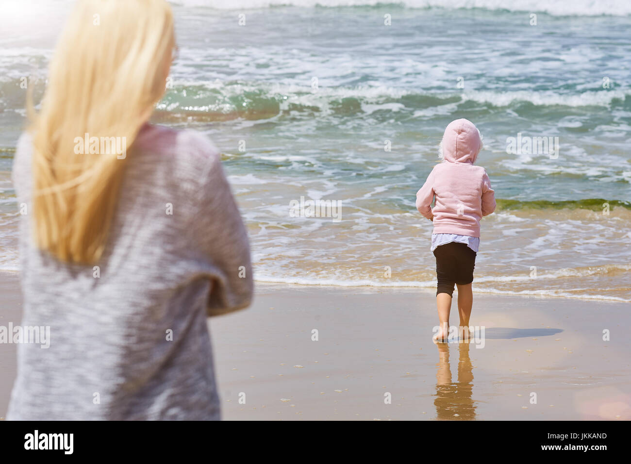 Mother and daughter play on the beach - Stock Image