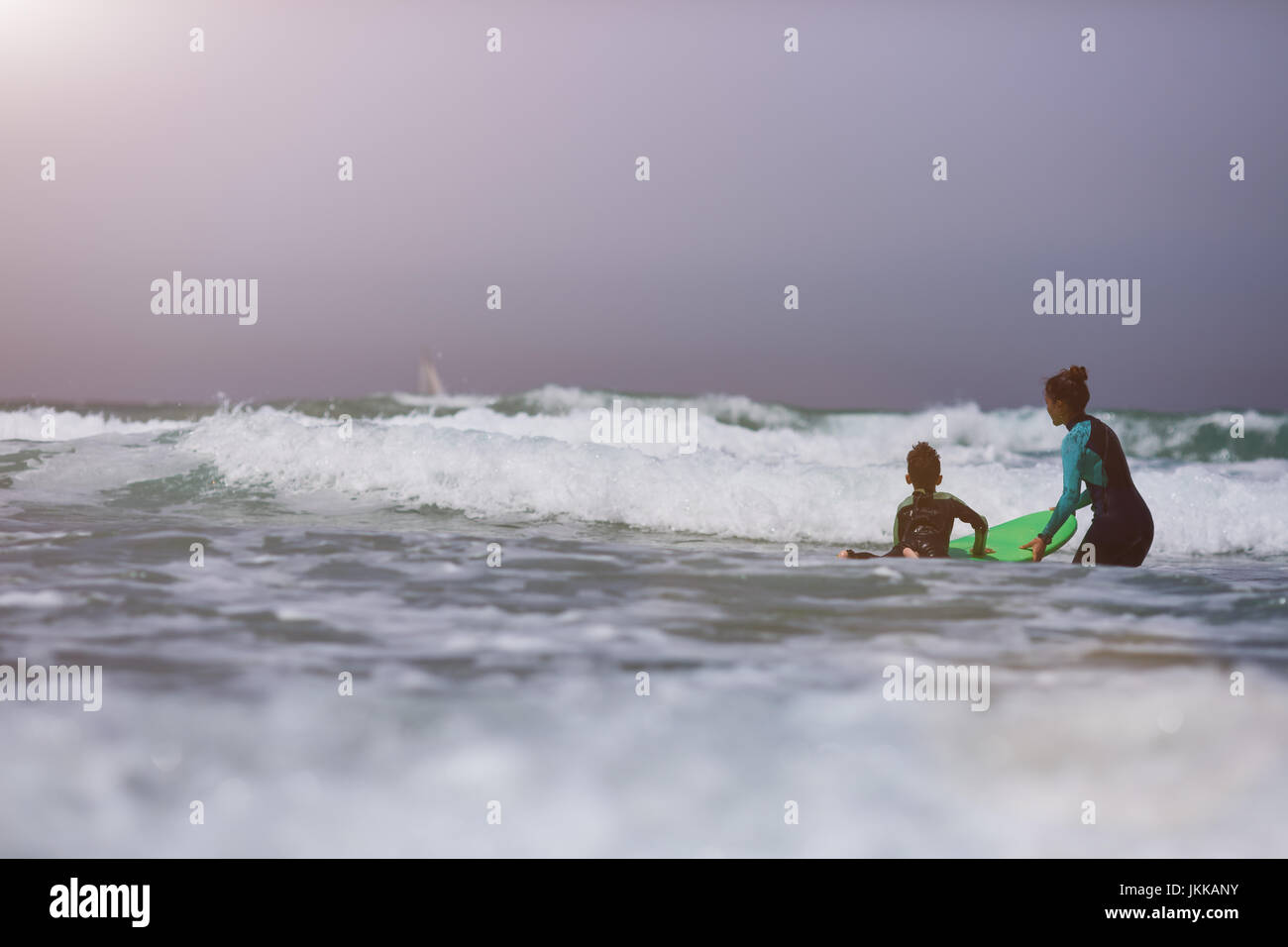 Athletic girl with little boy teaching him surfing - Stock Image