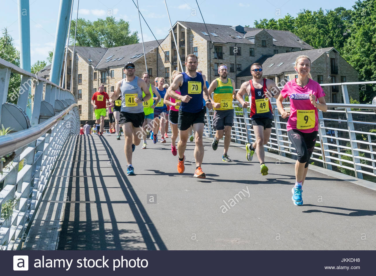 Runners cross the Millennium Bridge over the River Lune in Lancaster, England, as they take part in a running event - Stock Image