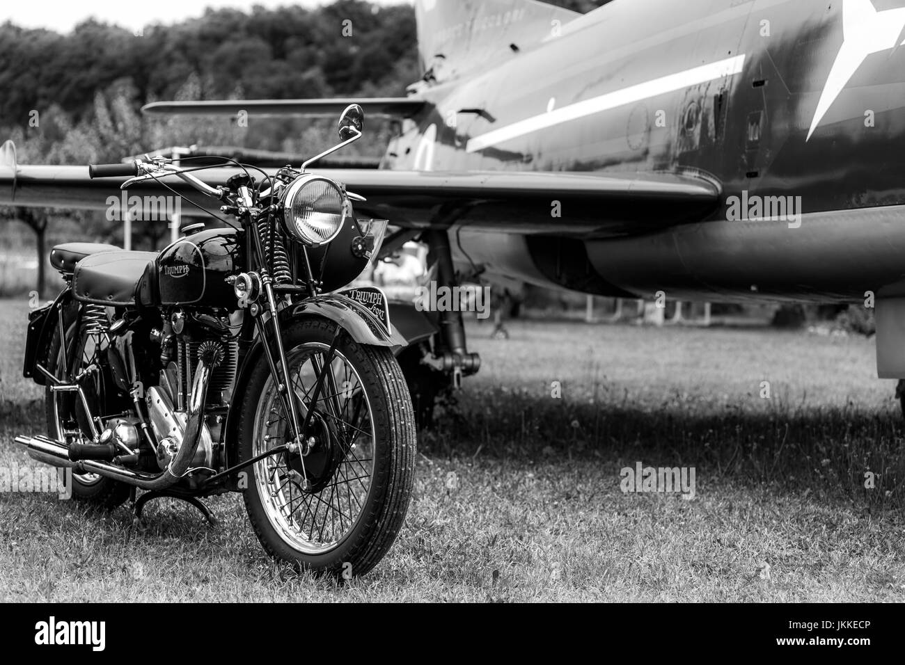 Old black motorcycle made by triumph motorcycles british brand with an airplane in the background black and white