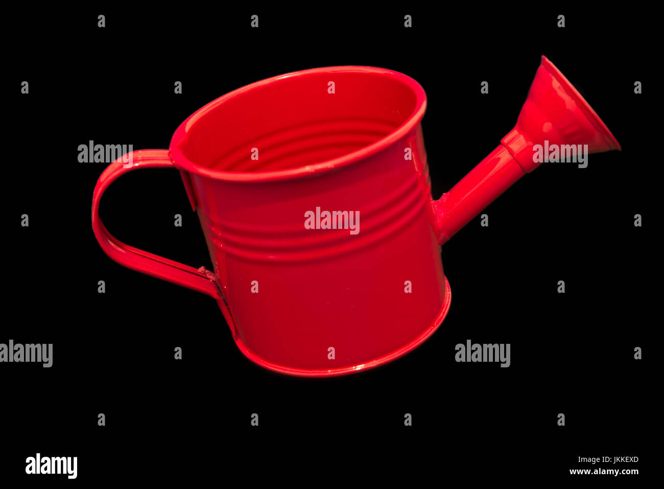 Single Red Watering can Isolated on Black Background. Image is clean and bright and centred in the image with room - Stock Image