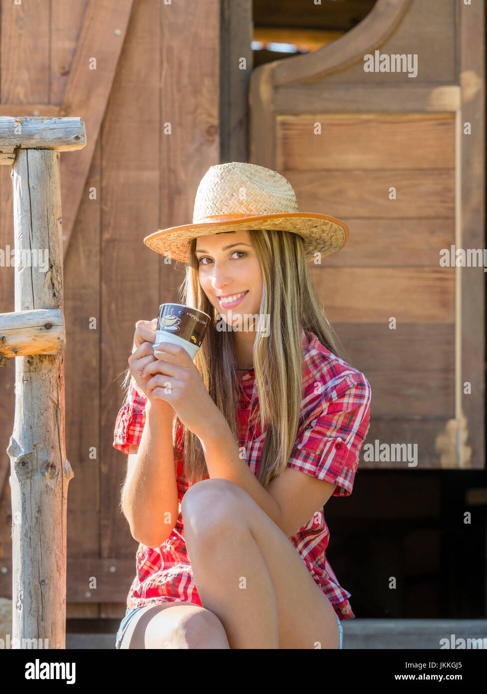 Countrygirl with cup of coffee in hand smiling smile single teenager giggling - Stock Image