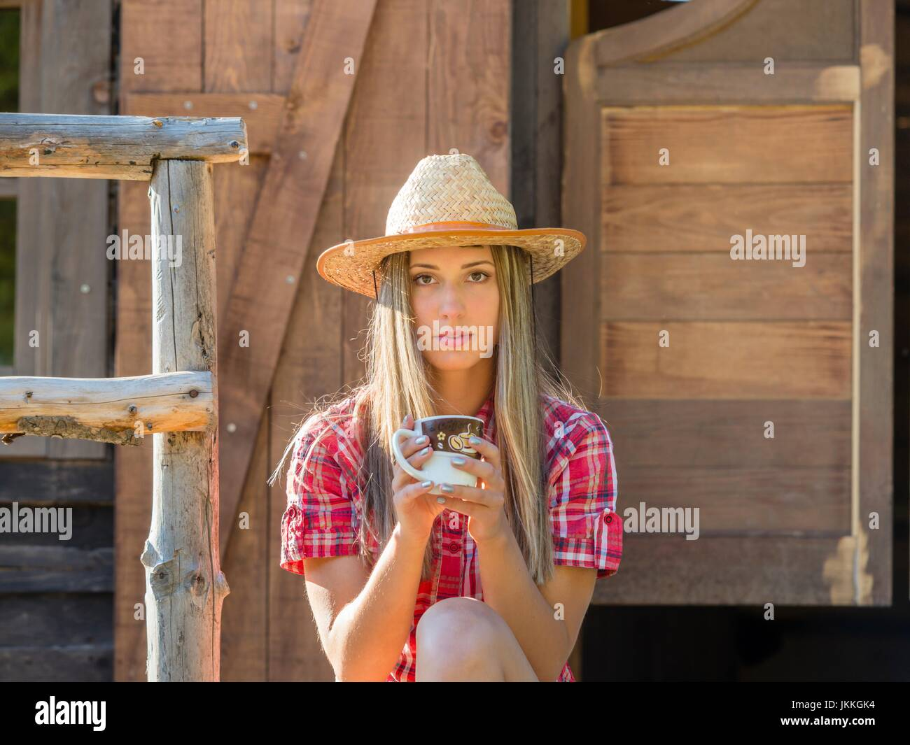 One country-girl with cup of coffee in hand facing camera serious looking at camera front frontal view - Stock Image