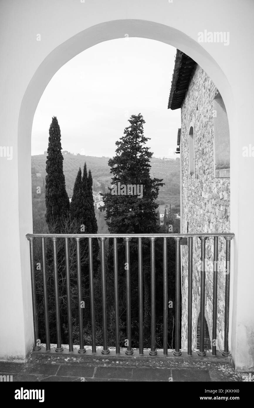 View of trees and building wall from an arch. Florence. Italy. Photo in black and white color style. - Stock Image