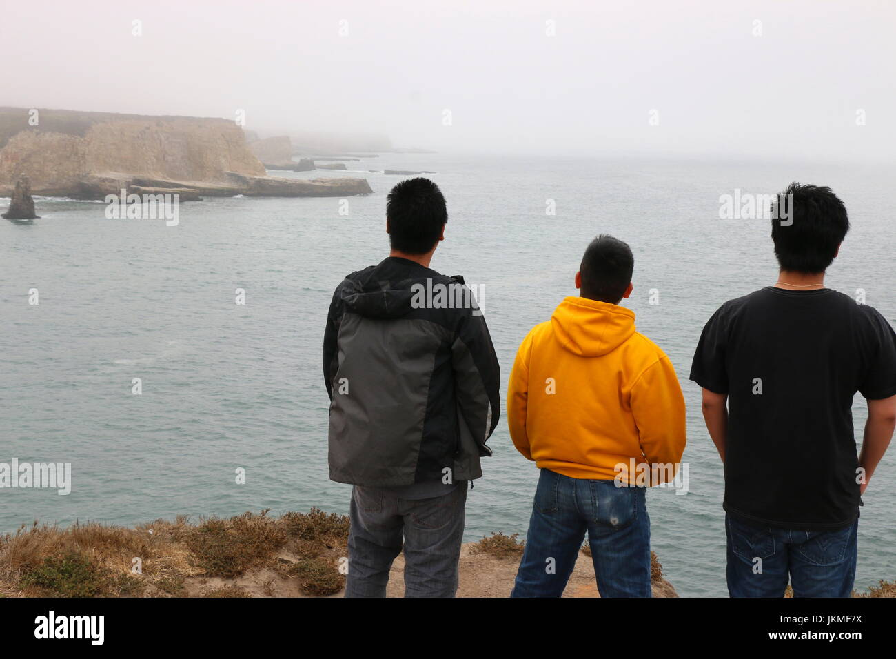 Three young Asian men on a hike overlooking the California coast, Davenport CA. - Stock Image