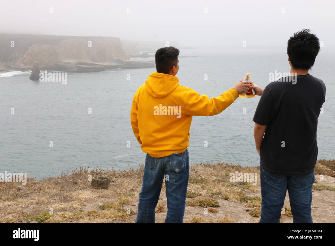 Two young Asian men raise a toast to the beautiful view, Davenport CA. - Stock Image