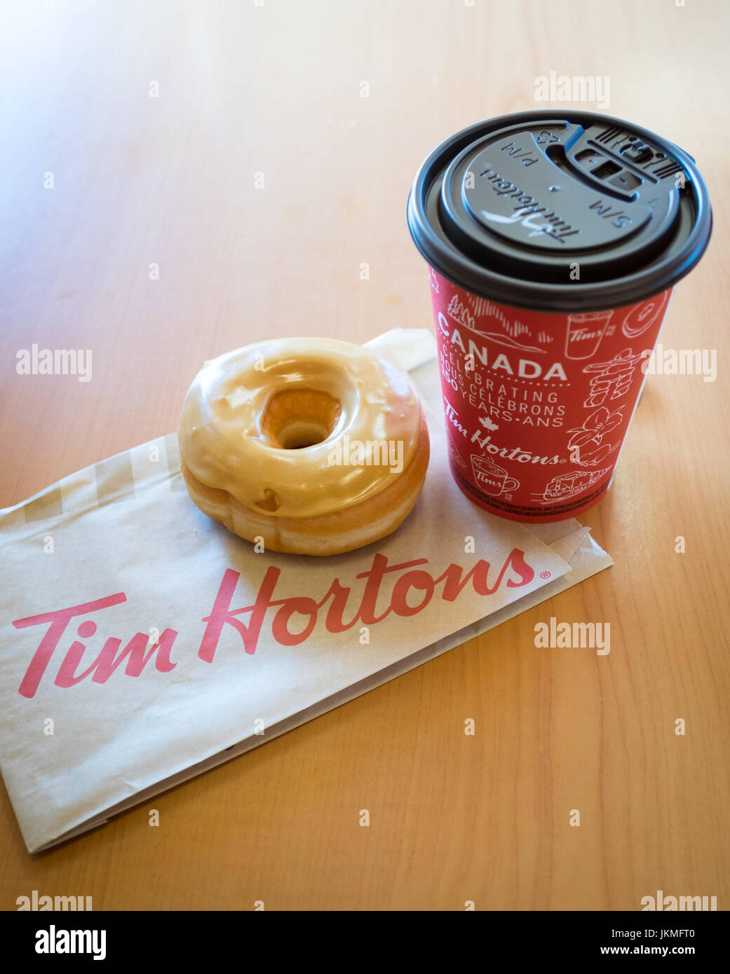 A Tim Hortons maple dip donut and coffee. - Stock Image