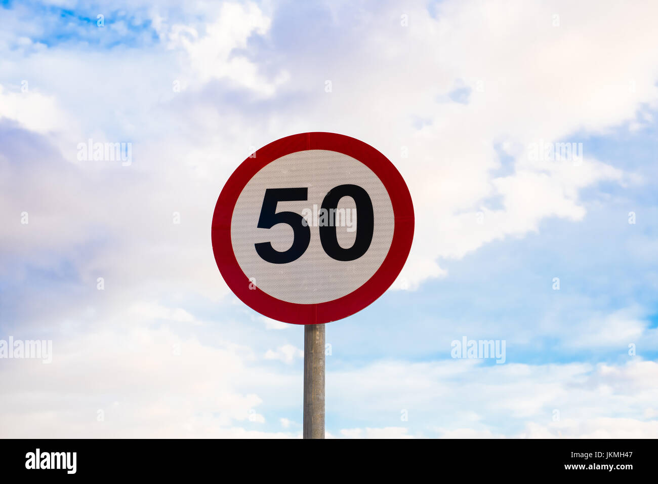 Road sign speed limit to 50, traffic sign in blue sky background Stock Photo