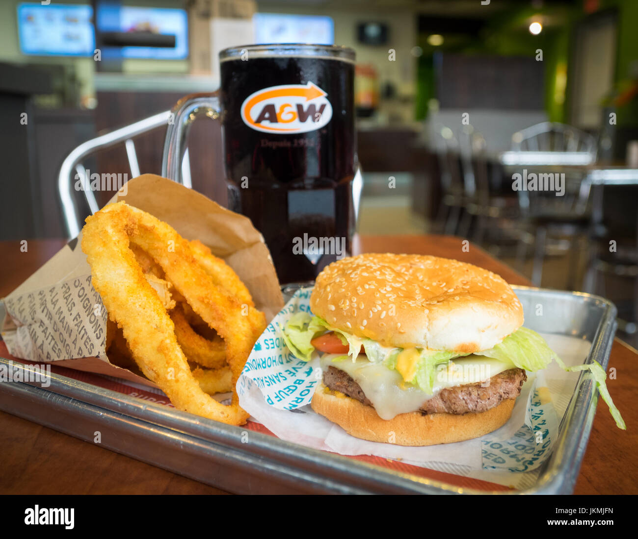 A Mozza Burger, onion rings, and mug of root beer from A&W, a Canadian fast food restaurant. - Stock Image
