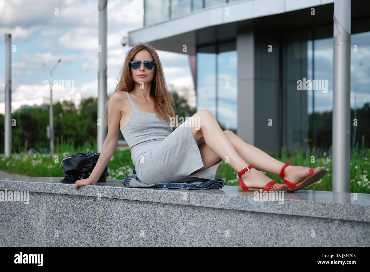Young attractive stylish brunette woman sitting on marble surface with bent knee. Reflection of the sky in windows. - Stock Image