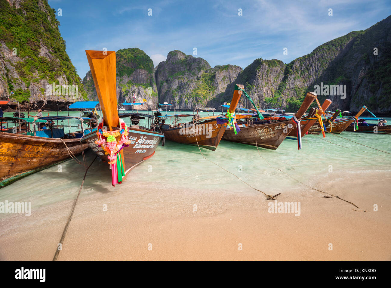 KRABI, THAILAND - DECEMBER 4 : Colorful long tail boats at beautiful beach on a background of blue sky and azure - Stock Image