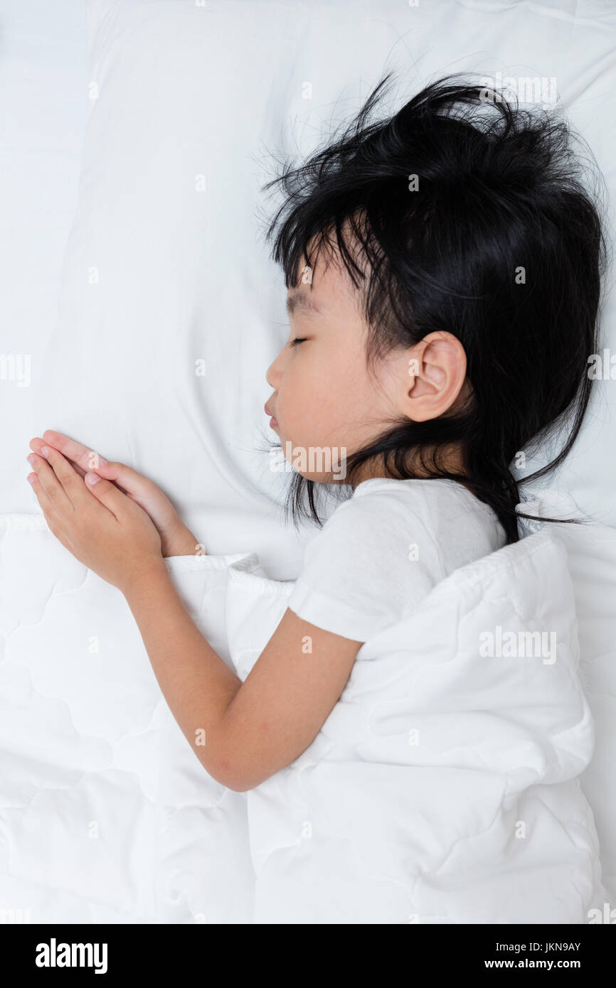 Asian little Chinese girl sleeping on the bed at home - Stock Image